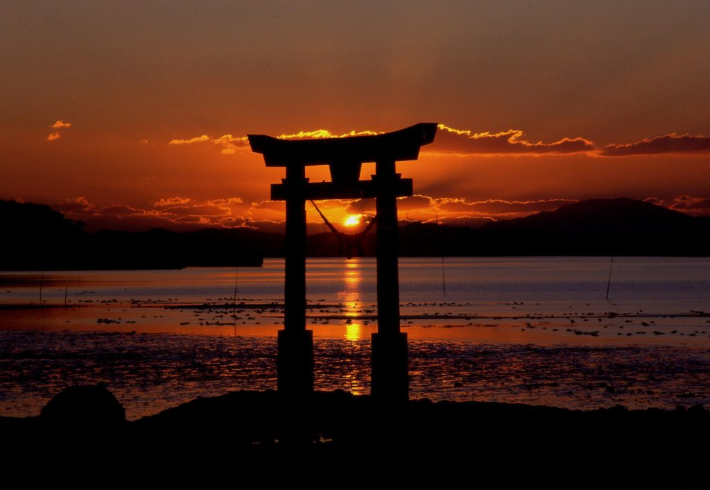 A japanese gate standing in a river